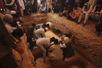 Families and friends bury the victims of the Dubai City wedding hall bombing during a mass funeral in Kabul on Sunday.