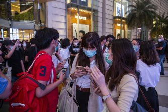 "Pro-democracy protesters check their phones for a 6pm ""big announcement"" from protest leaders on October 20 in Bangkok."