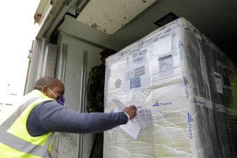 Seorang petugas bandara memeriksa pengiriman vaksin dari Yunani melalui Covax di Nairobi, Kenya.