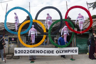 Exile Tibetans use the Olympic Rings as a prop as they hold a street protest against the holding of 2022 Winter Olympics in Beijing