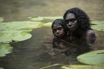 A young Gutjuk (Guruwuk Mununggurr) hiding in a waterhole with his mother Wak Wak (Magnolia Maymuru) during the massacre.