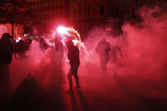 Riot police tear gas and and protesters' fireworks combine to add colour to the chaos.