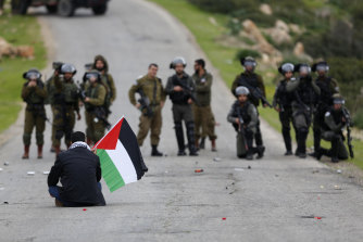 A Palestinian demonstrator sits in front of Israeli occupation troops during protests in the Jordan Valley in February.
