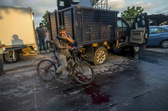 A man handles a bullet cartridge on a bloodied street.