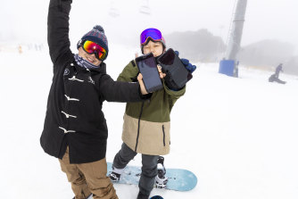 Jianfeng Ruan (left) and Zi Tao from Melbourne display their negative COVID-19 test text message as they enjoy their first runs of the season at Mount Buller.