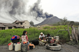 Villagers do their laundry as Mount Sinabung spews volcanic materials during an eruption, in Karo, North Sumatra, on Friday, August 14.