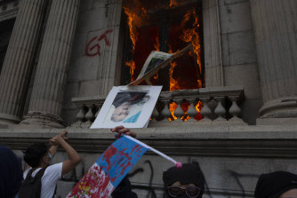 An official photo of former Congress President Eduardo Meyer is thrown out from the Congress building after protesters set a part of the building on fire, in Guatemala City, on Saturday, November 21.