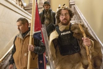 Insurrectionists loyal to President Donald Trump storm the US Capitol building on January 6 carrying a Confederate flag.