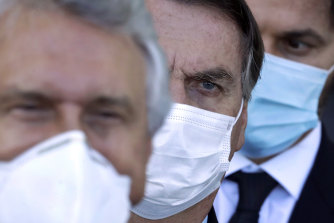 Brazilian President Jair Bolsonaro, centre, arrives for a press conference following a ministerial meeting about his government's handling of the pandemic.