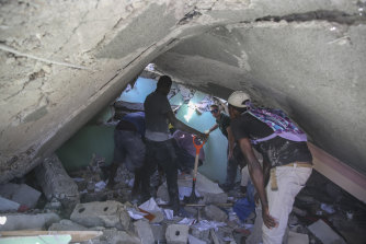 People search for survivors in a home destroyed by the earthquake in Les Cayes, Haiti.