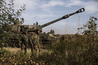 Two Israeli soldiers walk around an artillery unit, at the Israeli Gaza border, on Sunday, May 16.