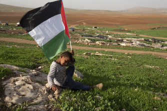 A boy holds a Palestinian flag after Israeli troops demolished tents and other structures of the Khirbet Humsu hamlet in the Jordan Valley in the West Bank on Wednesday.