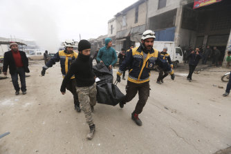 Emergency services carry the body of a person killed in a government air strike in the city of Idlib  on February 11.