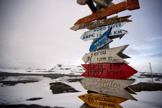Wooden arrows show the distances to various cities on King George Island, Antarctica.