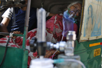 A coronavirus patient wearing an oxygen mask waits inside an auto rickshaw to be admitted to a dedicated COVID-19 government hospital in Ahmedabad, India, on Saturday.