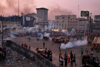 Anti-government protesters gather while Iraqi forces fire tear gas during a demonstration in Tahrir Square in Baghdad on Monday.