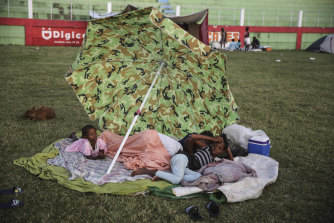 People rest after spending the night at a soccer field following a 7.2 magnitude earthquake in Les Cayes, Haiti.
