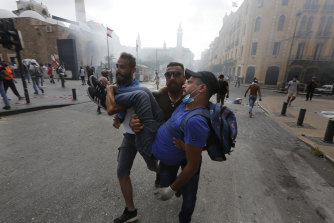 Protesters carry a wounded man during demonstrations on August 8, in Beirut, Lebanon.