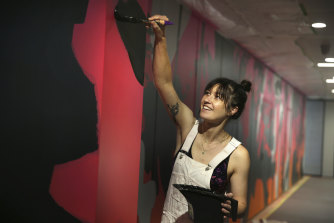 George Rose and the mural she is painting on the walls of TikTok's Sydney offices.