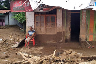 A man sits among flood debris in front of his home in the village of Waiwerang, on Adonara Island, eastern Indonesia.