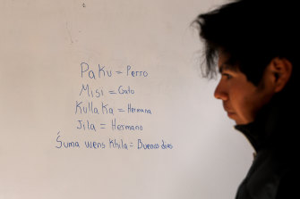 Jose Choque stands next to words he wrote on a school whiteboard in the Uru language.