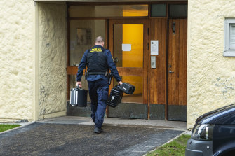 Police enter the apartment block where the man was found.