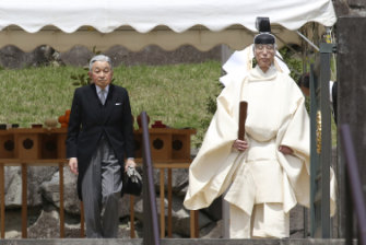 A Shinto priest leads Akihito from the tomb of his late father, Hirohito, who Akihito has just informed of his impending retirement.