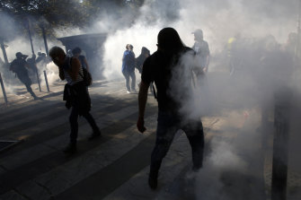 Protesters enveloped by tear gas during the climate demonstration in Paris.