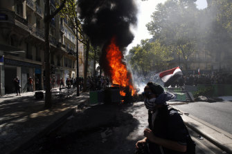 A protester walks past a burning barricade in Paris on Saturday.