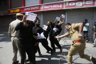 An Indian police officer charges at Kashmiri Shiite Muslims as they attempt to take out a religious procession.