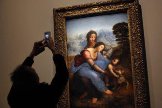 "A journalist takes a snapshot of the ""The Virgin and Child with Saint Anne""."