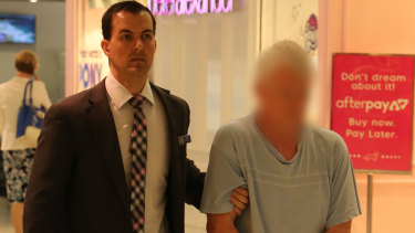 A 67-year-old man is escorted through Sydney Airport, after he was extradited from Queensland on historic sexual abuse charges.