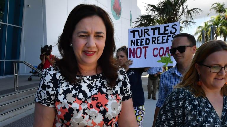 Queensland Premier Annastacia Palaszczuk walks past an anti-Adani coal mine protester as she leaves the Cairns Aquarium on Wednesday.