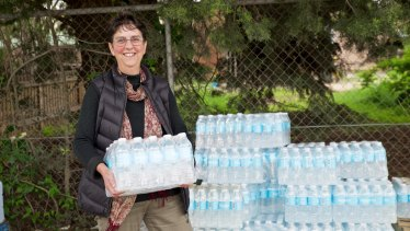 Local resident Jenny Evans picks up a stash of bottled water, which has been provided for all Uralla residents since December.