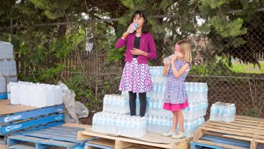 Maria Evans, niece of Jenn Evans, and Matilda Seath-Robinson with pallets of bottled water in Uralla.