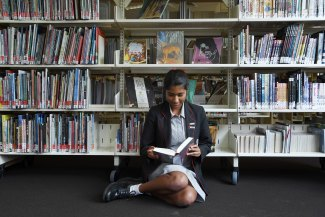 Amisha Guta, 16, reading in the library at Queenwood school in Mosman.