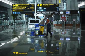 A cleaner walks through the nearly empty Soekarno-Hatta International Airport in Jakarta, Indonesia.