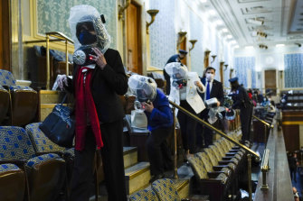 People shelter in the House of Representatives gallery as protesters try to break into the chamber at the US Capitol.
