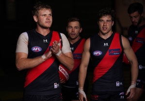 Michael Hurley (left) leads the Bombers out for their opening-round clash with Fremantle.