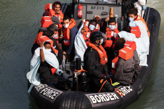 British Border Force officials take migrants who have been intercepted in the English Channel for processing in September, in Dover, England.