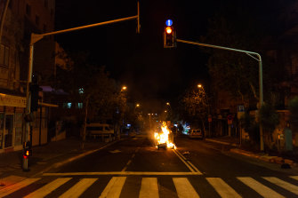 A fire started by rioters in the middle of the street in the Hadar suburb of Haifa, Israel.