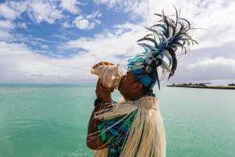 A local blows into a conch shell as he welcomes visitors to Aitutaki.