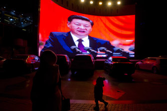 A child walks past a large screen showing Chinese President Xi Jinping near a carpark in Kashgar, western China.