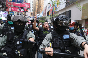 Tam Tak-chi, vice-chairman of Hong Kong's People Power party, is led away by riot police during a protest against Beijing's plans for tough new security laws in the former British colony.