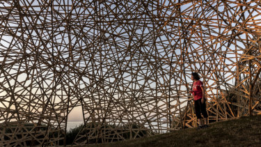 A woman looks over a sculpture by Australian artist Cave Urban titled Transcience.