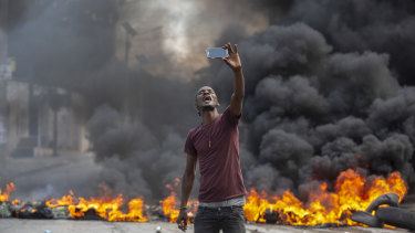 A protester takes a selfie at a burning barricade in Port-au-Prince, Haiti, on Monday.