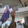 A protester at a Hong Kong shopping mall holds up a colonial flag and a British National Overseas passport.