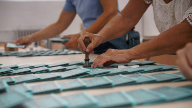 Volunteers stamp ballots at a polling station in Rome.