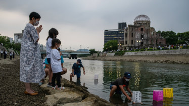 A family prays as paper lanterns are floated on the Tenma River to mark the 75th anniversary of the Hiroshima bombing.