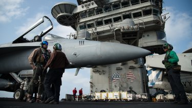 """A pilot speaks to a crew member by an F/A-18 fighter jet on the deck of the USS Abraham Lincoln aircraft carrier in the Arabian Sea. Donald Trump has threatened Iran with """"obliteration""""."""